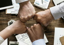 Hands fist bumping over conference table